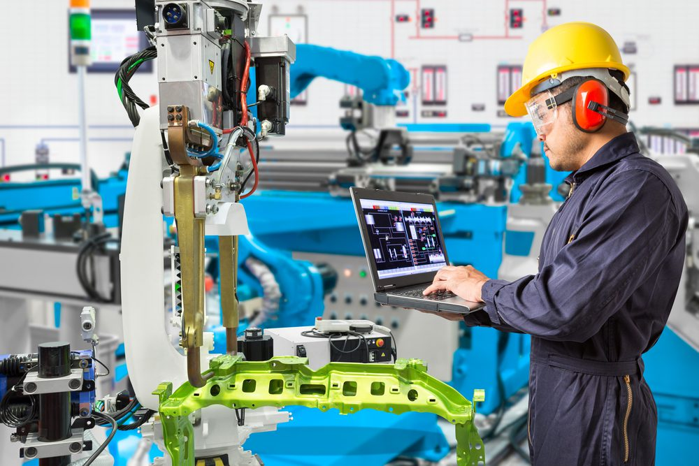Engineer working on a laptop in an automated manufacturing facility