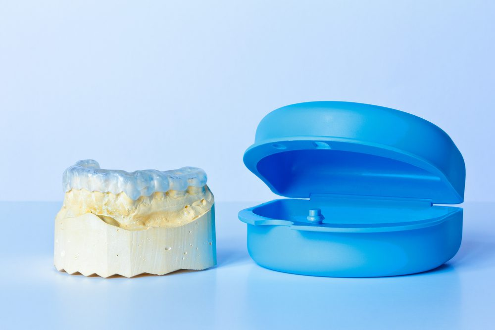 A custom-made night guard, oral mold, and container