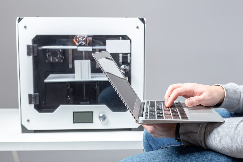 A designer works from a laptop with a 3D printer